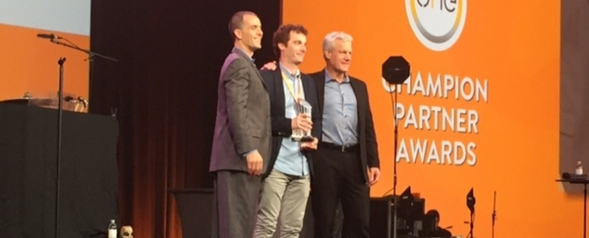 Three men on stage accepting an award