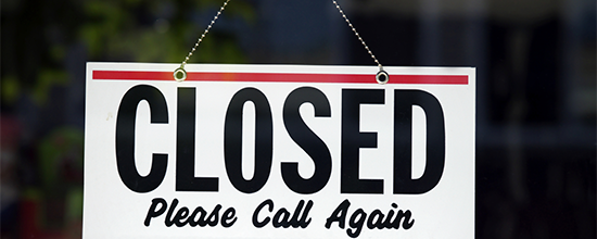 An image of a traditional 'Closed for business' window flip sign on a chain.